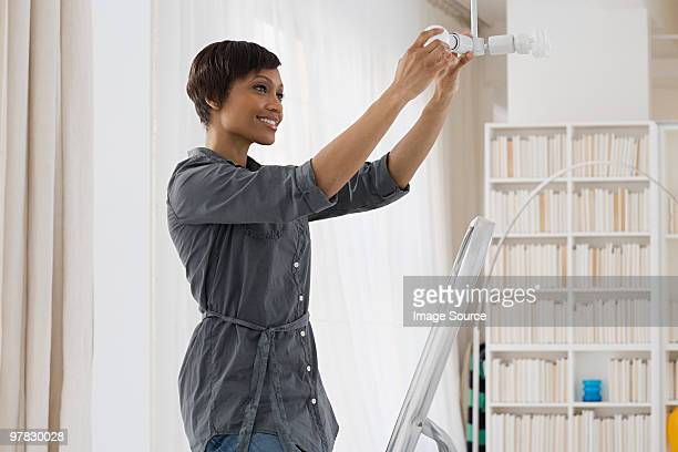 woman fitting lightbulb - light bulb stock pictures, royalty-free photos & images