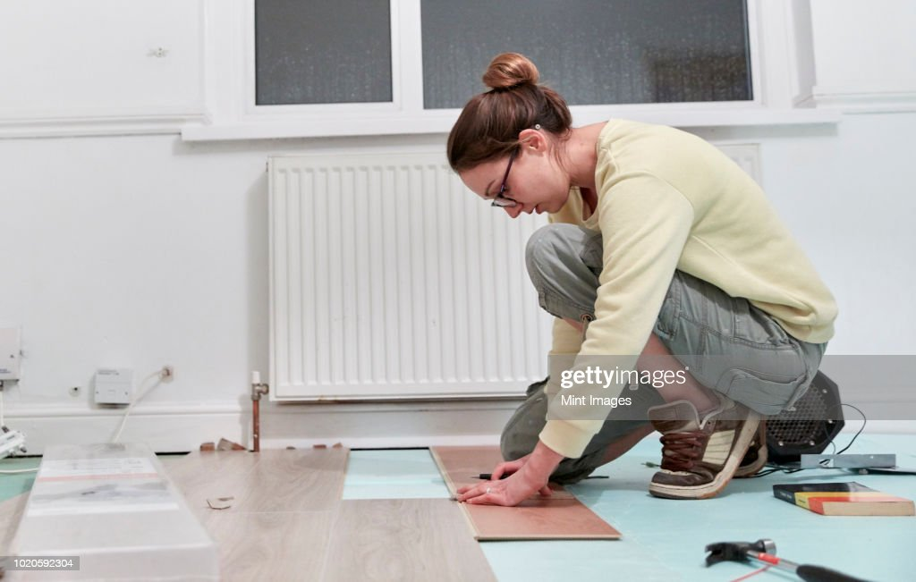 Woman fitting new floor boards, house renovation : Stock Photo
