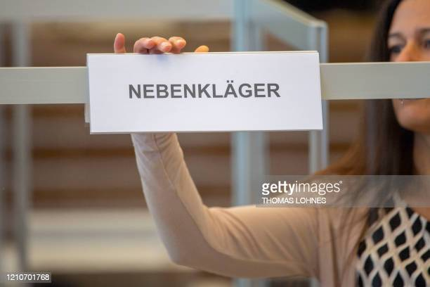 A woman fixes a sign at a place reserved for a joint plaintiff at the courtroom prior to the start of a trial against two Syrian defendants accused...