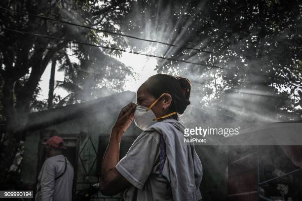 A woman fixes her face mask amidst heavy ashfall from Mount Mayon's eruption in Guinobatan Albay province Philippines January 23 2018 Mount Mayon the...