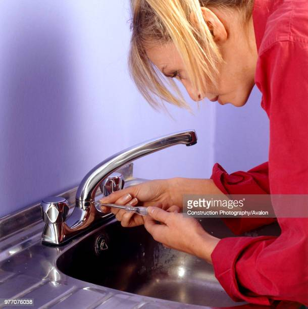 Woman fixing a new tap and kitchen sink