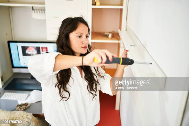 woman fixing a shelf at home with a screwdriver - home improvement stock pictures, royalty-free photos & images