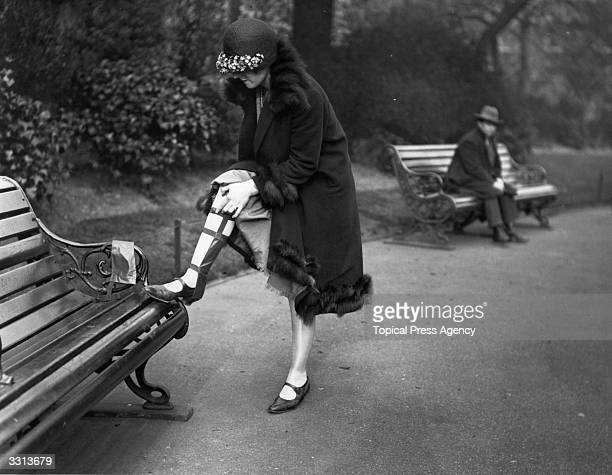 A woman fixing an antisplash gaiter to her leg a device to keep stockings clean in muddy weather