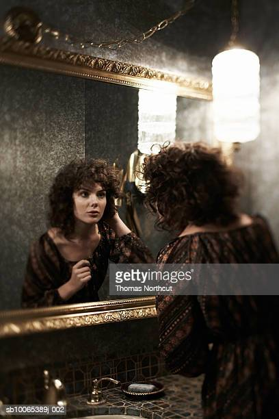 Woman fixing hair in bathroom