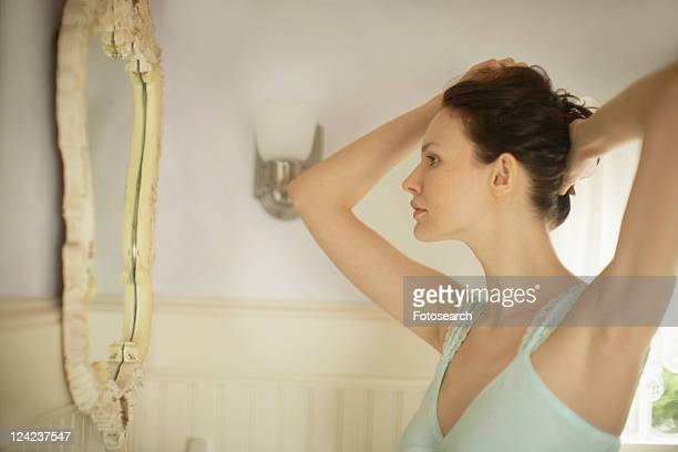 Woman fixing hair in front of mirror