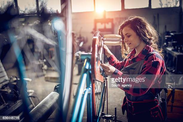 Woman fixing her bicycle
