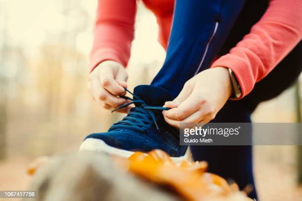 Woman fixing her shoelaces before jogging.