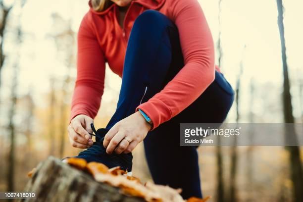woman fixing her shoelaces before jogging. - pantalón naranja fotografías e imágenes de stock