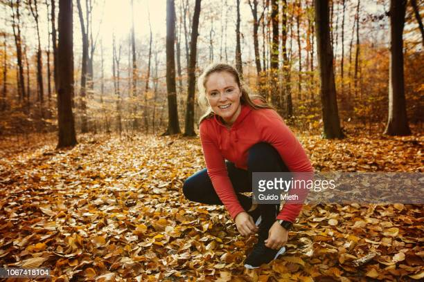 Woman fixing her shoelaces in a forest.