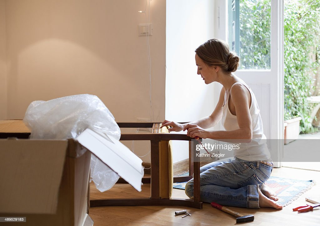 woman fixing piece of furniture : Stock Photo