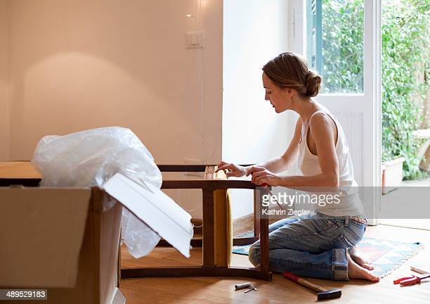 woman fixing piece of furniture - hausdekor stock-fotos und bilder
