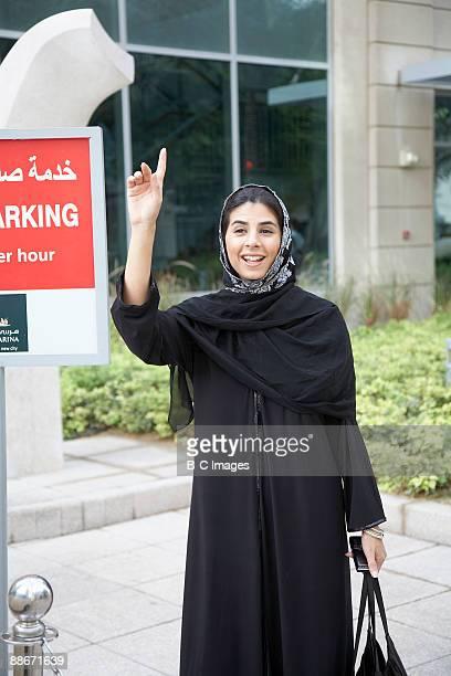 Woman flagging down a taxi, Dubai, UAE