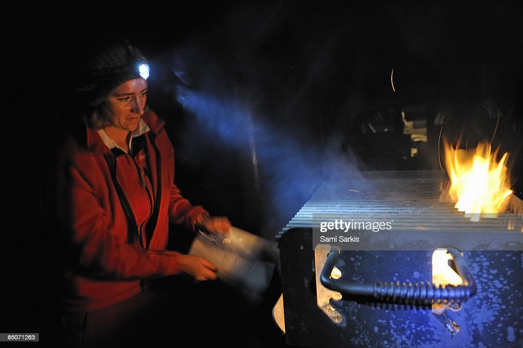 Woman flaming barbecue coals at night : Stock Photo