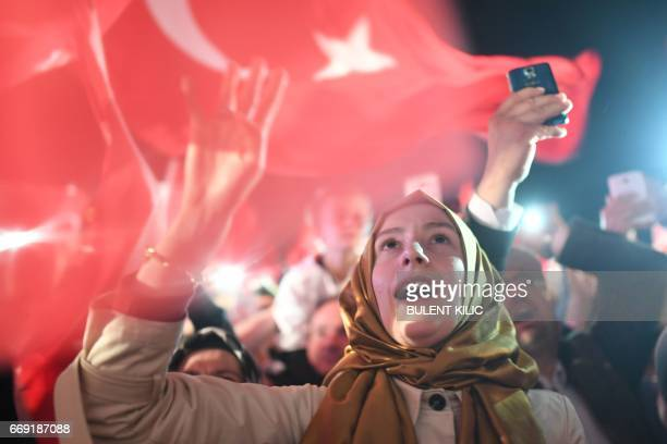 TOPSHOT A woman flashes a four finger sign called 'the rabia sign' as she celebrates and greets Turkish president during his speech at the...