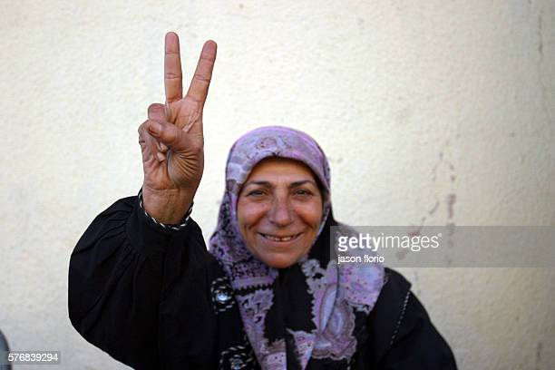 A woman flashes a peace sign Photo by Jason Florio/Corbis