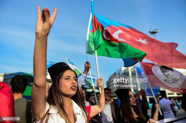 A woman flashes 'grey wolf' nationalist sign as protesters wave Turkish and Iraqi Turkmen flags on September 24 2017 in Istanbul during a...