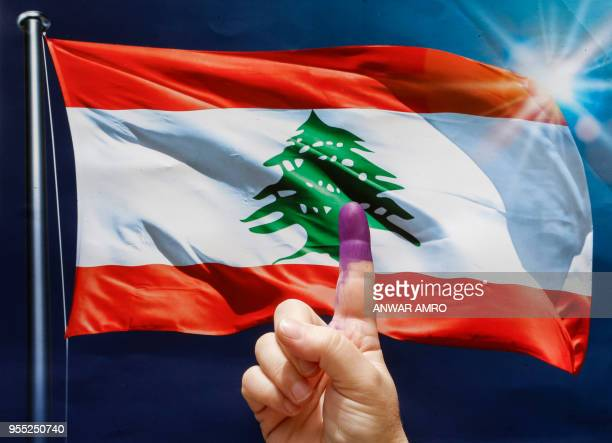 A woman flashes her inkstained index finger before a poster depicting a waving Lebanese flag after voting at a polling station in the capital Beirut...