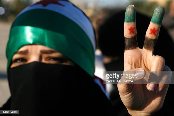 A woman flashes the V for 'victory' sign with her fingers painted in the colours of the former Syrian flag during a protest against the Syrian regime...