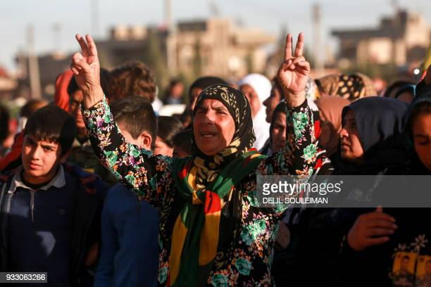 A woman flashes the victory gesture with both her hands as she attends the funeral of fighters of the People's Protection Units in the northeastern...