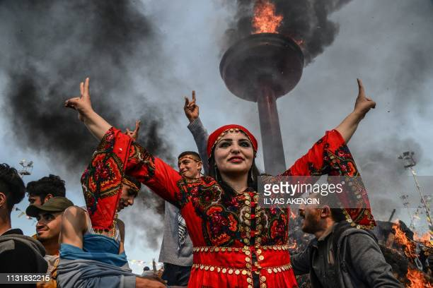 TOPSHOT A woman flashes the victory sign in front of a bonfire as Turkish Kurds gather during Newroz celebrations for the new year in Diyarbakir...