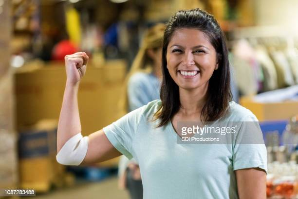 Woman flexes muscles after donating blood
