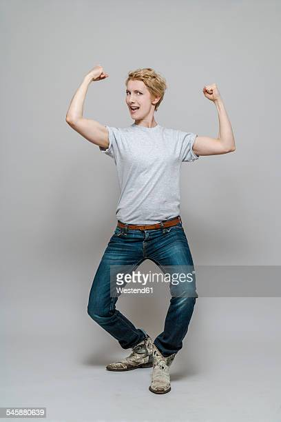 woman flexing her muscles in front of grey background - flexing muscles stock pictures, royalty-free photos & images