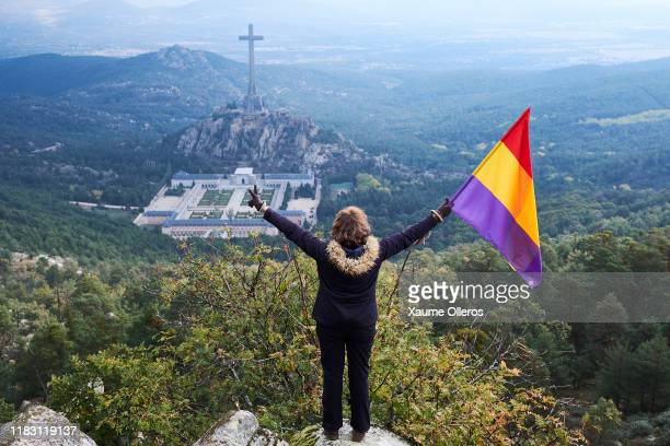 A woman flies a republican flag on top of a hill as she waits for the exhumation of former Spanish dictator Francisco Franco on October 24 2019 in...