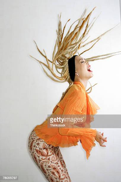 woman flinging dreadlocks over her head - dreadlocks stock pictures, royalty-free photos & images