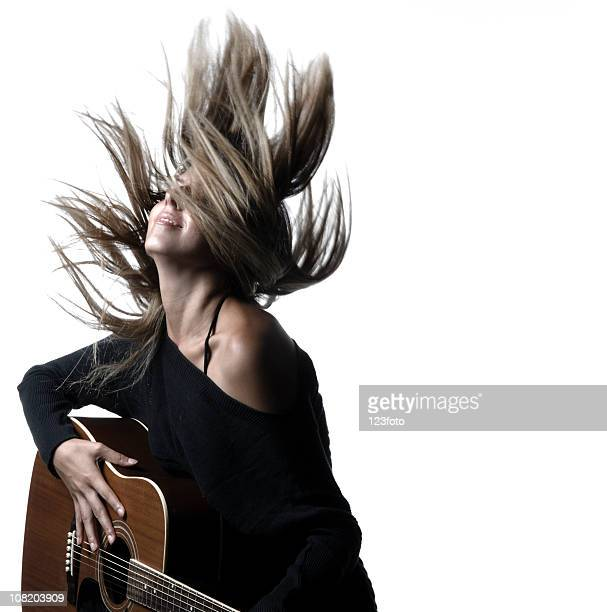 woman flipping hair and holding guitar - rocker stock photos and pictures