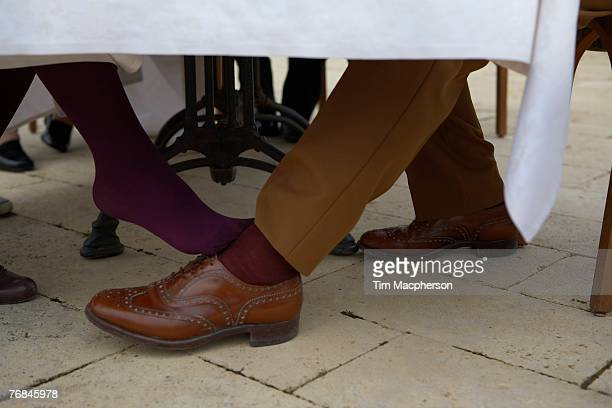 woman flirting with man under table - playing footsie stock photos and pictures