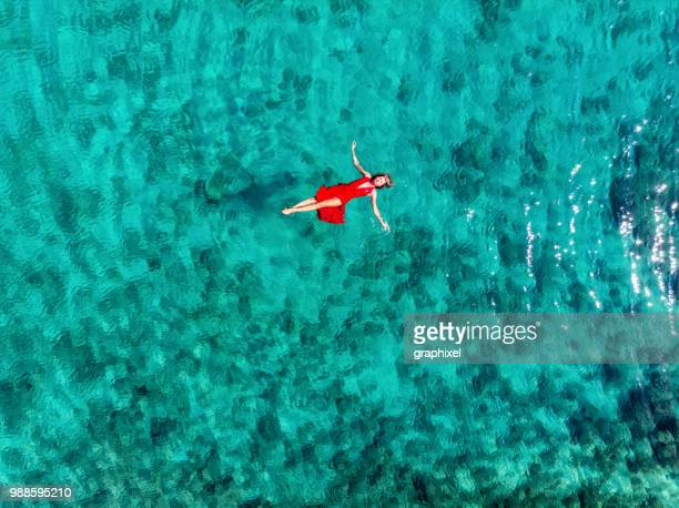 woman floating and swimming on a tropical sea - lagoon stock pictures, royalty-free photos & images