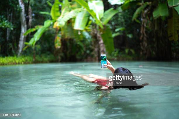 woman floating and taking pictures exploring fervedouro in tocantins, brazil - palmas tocantins imagens e fotografias de stock