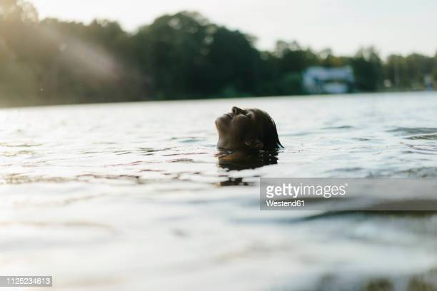 woman floating in a lake at sunset - auf dem wasser treiben stock-fotos und bilder