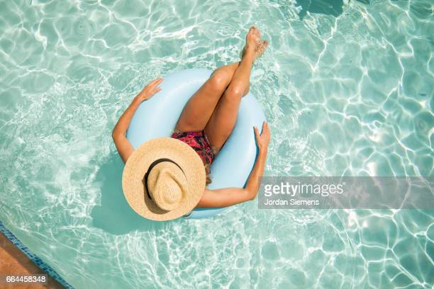 a woman floating in a pool. - badkleding stockfoto's en -beelden