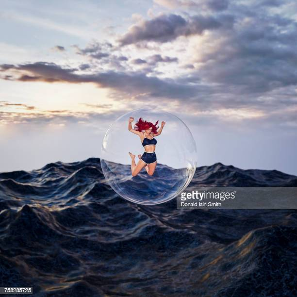 Woman floating in bubble over stormy ocean