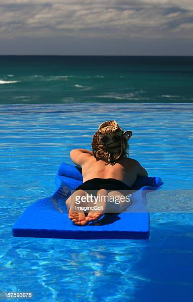 Woman Floating in Infinity Pool