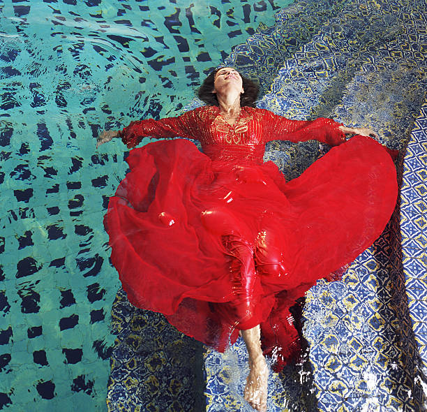 Woman floating in pool, wearing red dress, elevated view