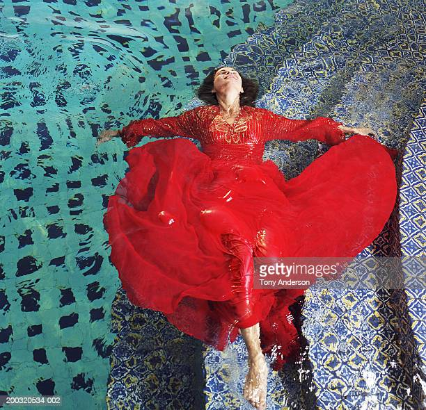 woman floating in pool, wearing red dress, elevated view - red dress stock pictures, royalty-free photos & images