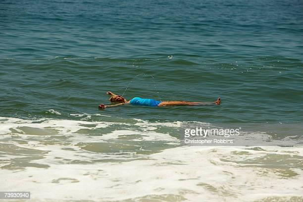 Woman floating in sea, full length