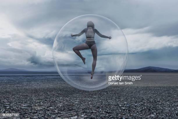 Woman floating in sphere in remote landscape