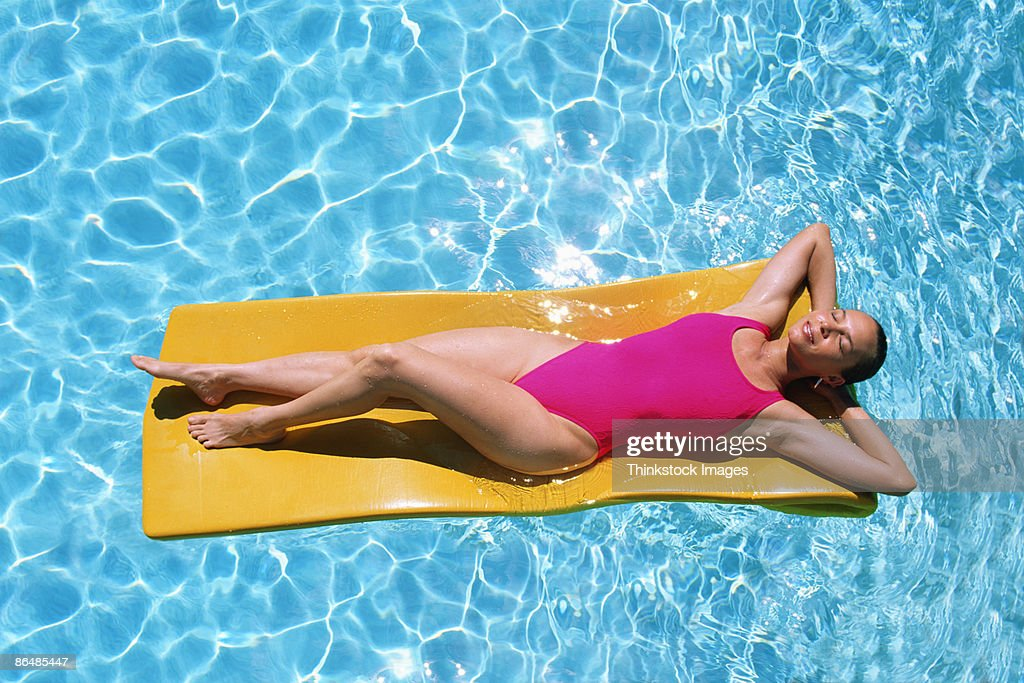 Woman floating in swimming pool : Stock Photo