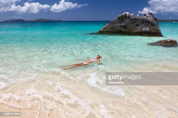 熱帯のビーチで水に浮かぶ女性、処女ゴルダ - バージン諸島 ストックフォトと画像