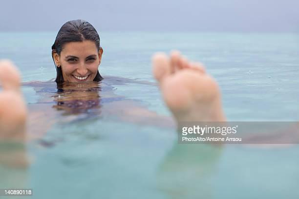 Woman floating in water, portrait