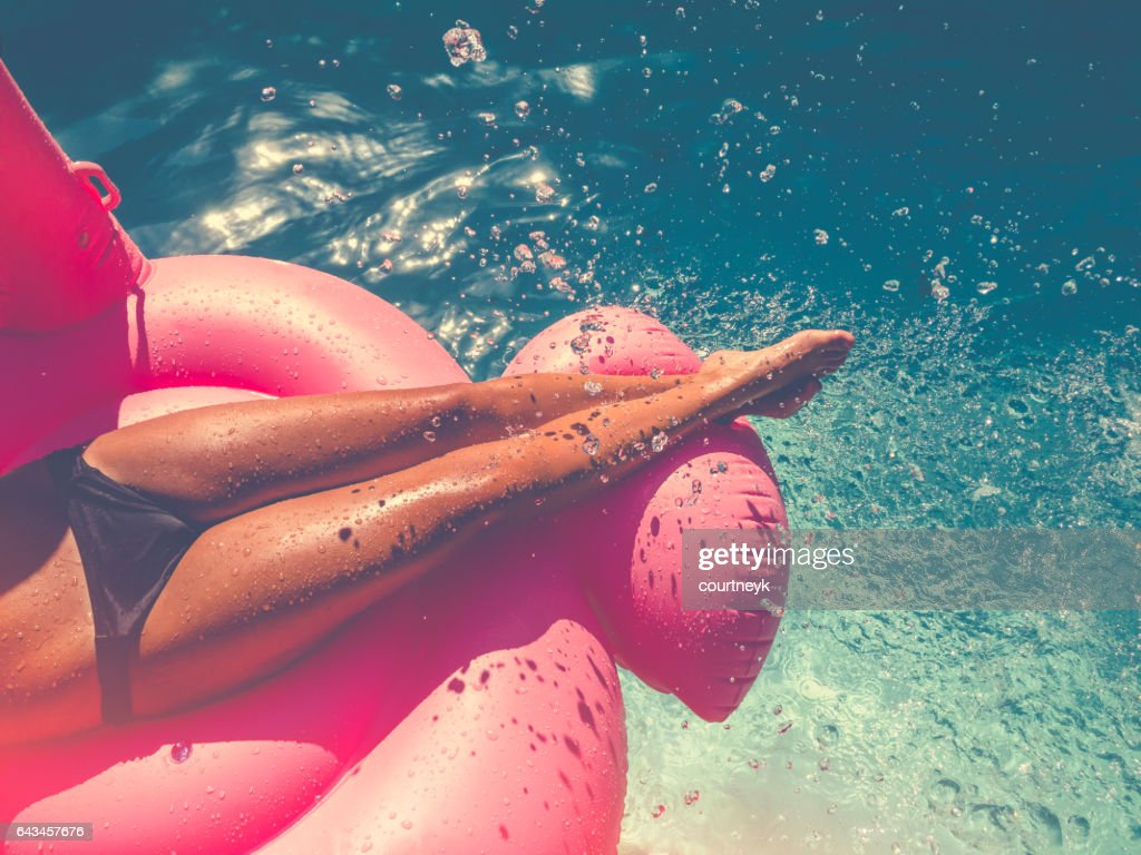 Woman floating on a pink inflatable in swimming pool. : Stock Photo