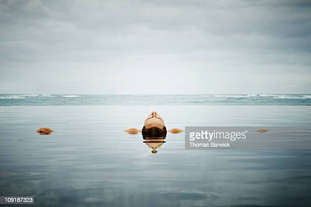 Woman floating on back in infinity pool