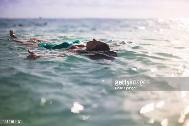 woman floating on back in sea - sint maarten caraïbisch eiland stockfoto's en -beelden