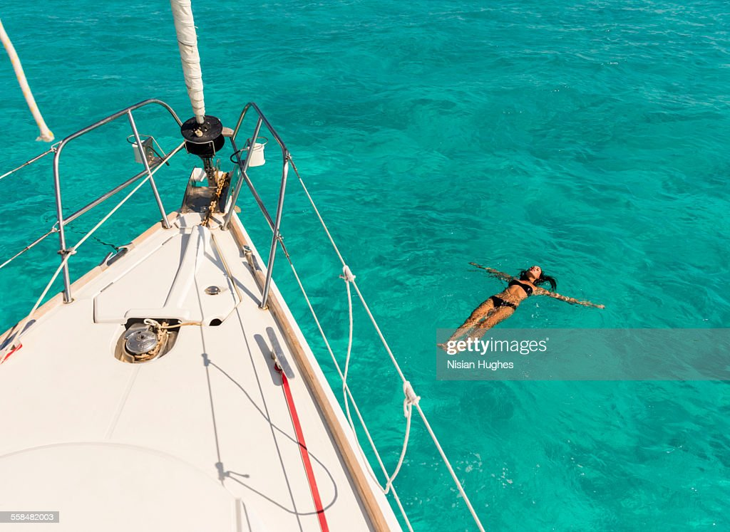woman floating on back, swimming next to sailboat : Stock Photo
