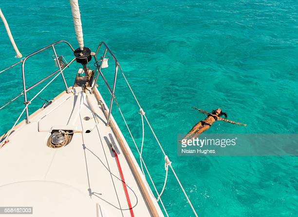 woman floating on back, swimming next to sailboat