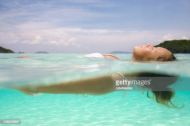 woman floating on crystal clear water in the Caribbean