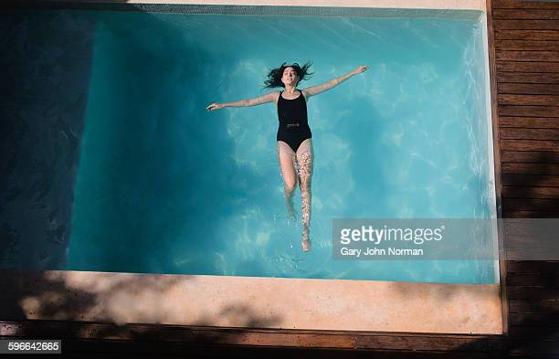 woman floating on her back in pool. - arms outstretched stock pictures, royalty-free photos & images